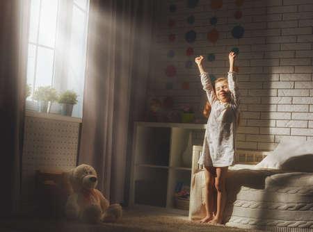 despertar: Una buena chica niño disfruta mañana de sol. Buenos días en casa. La muchacha del niño se despierta de su sueño. Foto de archivo