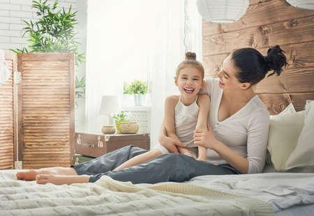 madre e hija: amante de la familia feliz. La madre y su hija juego muchacha niño y abrazos.