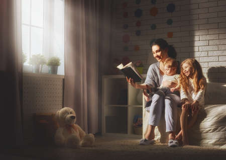 bedtime story: Family reading bedtime. Pretty young mother reading a book to her daughters.