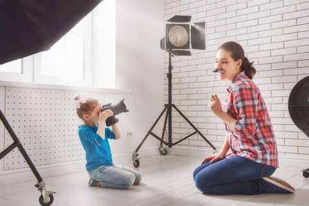 studio model: Photographer in motion. Young woman photographer and child girl having fun at the photo session. Stock Photo