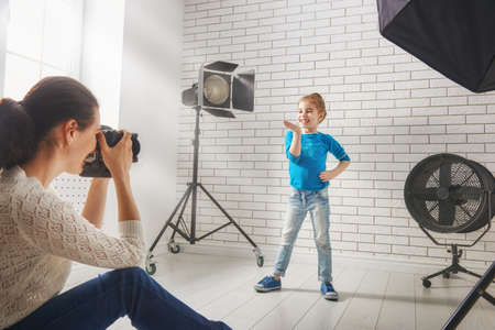 female photographer: Photographer in motion. Young woman photographs of the child.