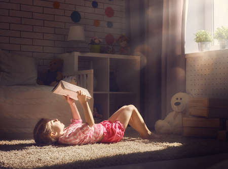 Cute little child girl reading a book.