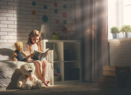 Cute little child girl reading a book. Kid girl sitting in her bed. Stock Photo