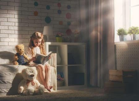 niña niño lindo leer un libro. chica niño sentado en su cama.