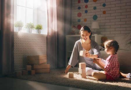 Gelukkig liefdevolle familie spelen met blokken en plezier maken. Moeder en haar kind dochter meisje samen spelen. Stockfoto