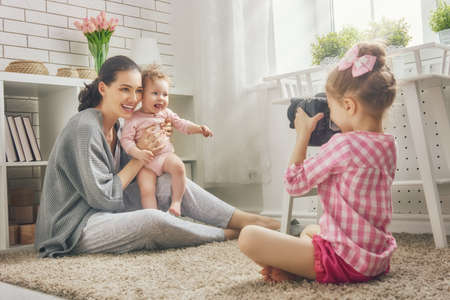 Happy loving family. Mother and her daughters children girls playing and making photo. 写真素材
