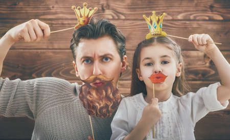 재미 가족! 아버지와 종이 액세서리와 함께 자신의 자식 딸 소녀. 스틱에 종이 입술과 왕관을 들고 뷰티 재미 있은 소녀. 아름 다운 젊은 남자 막대기에