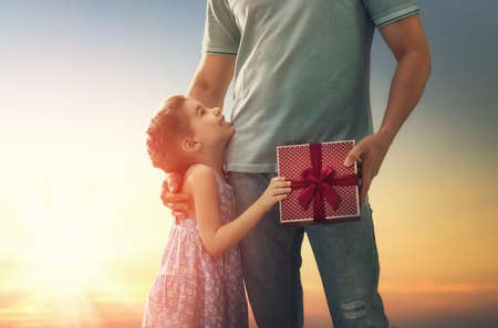 Happy loving family and Fathers Day. Father and his daughter. Cute child girl gives a gift to dad.
