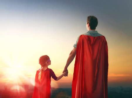 Felice famiglia amorevole. Padre e la sua ragazza figlia bambino che gioca all'aperto. Papà e la sua ragazza del bambino in costume di un supereroe. Il concetto di festa del papà.