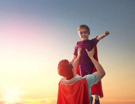 행복 한 사랑 가족. 아버지와 그의 딸 자식 소녀 야외에서 연주. 아빠와 슈퍼 히어로의 의상 그녀의 아이 소녀. 아버지의 날의 개념입니다. 스톡 콘텐츠