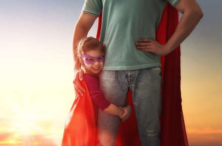 father daughter: Happy loving family. Father and his daughter child girl playing outdoors. Daddy and his child girl in an Superheros costumes. Concept of Fathers day.