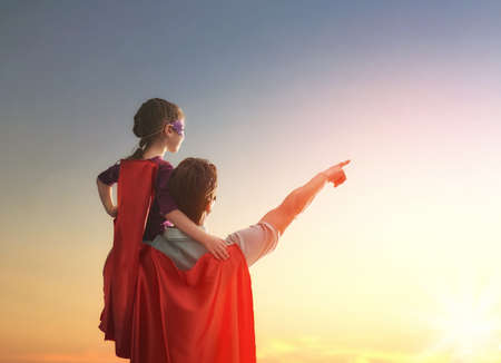 Šťastný milující rodina. Otec a jeho dcera dítě dívka hrát venku. Tatíček a jeho dítě dívka v kostýmech superhrdiny. Koncept den Otce.