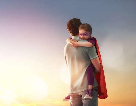 amante de la familia feliz. Padre y su hija niña niño que juega al aire libre. Papá y su muchacha del niño en el vestuario de un super héroe. Concepto del día de padre. Foto de archivo