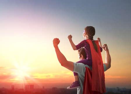 Felice famiglia amorevole. Padre e la sua ragazza figlia bambino che gioca all'aperto. Papà e la sua ragazza del bambino in costume di un supereroe. Il concetto di festa del papà. Archivio Fotografico