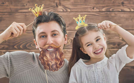 Funny family! Father and his child daughter girl with a paper accessories. Beauty funny girl holding paper crown on stick. Beautiful young man holding paper beard and crown on stick.