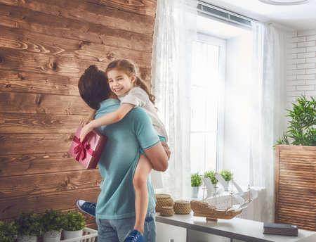 행복 한 사랑의 가족과 아버지의 날입니다. 아버지와 그의 딸. 귀여운 아가씨 아빠에게 선물을 제공합니다. 스톡 콘텐츠