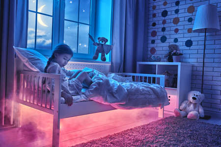 Nightmare for children. Little child girl is afraid of monsters in the dark of night. Frightened little girl and her teddy bear friend are protected against monsters. Stockfoto