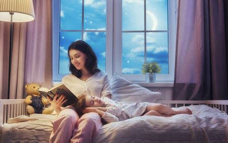 Family reading bedtime. Pretty young mother reading a book to her daughter. Stock Photo