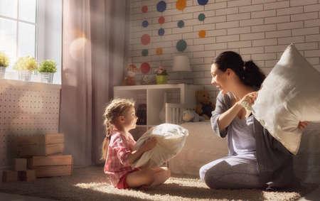 niños riendose: ¡Familia feliz! La madre y su muchacha del niño están luchando almohadas. juegos felices de la familia. Foto de archivo