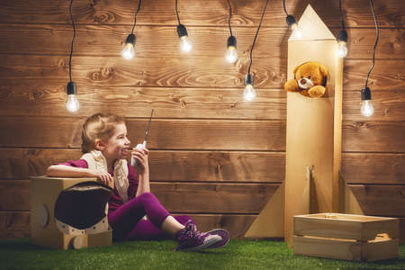 lamp light: Child girl in an astronaut costume with toy rocket playing and dreaming of becoming a spacemen. Stock Photo