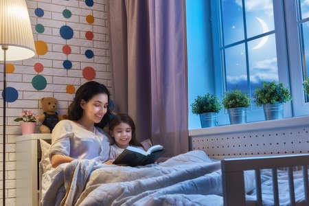 가족 취침 읽기. 꽤 젊은 어머니는 그녀의 딸이 책을 읽고.