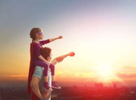 Amante de la familia feliz. Padre y su hija niña niño que juega al aire libre. Papá y su muchacha del niño en el vestuario de un super héroe. Concepto del día de padre. Foto de archivo - 57628888