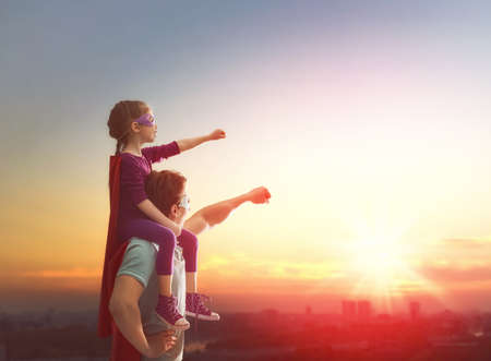 Happy loving family. Father and his daughter child girl playing outdoors. Daddy and her child girl in an Superhero's costumes. Concept of Father's day. Stok Fotoğraf - 57628888