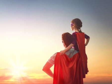 inspiracion: amante de la familia feliz. Padre y su hija niña niño que juega al aire libre. Papá y su muchacha del niño en el vestuario de un super héroe. Concepto del día de padre.