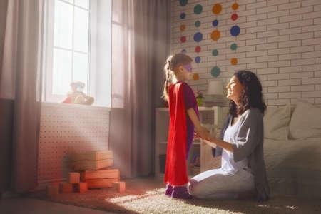 Gelukkige liefdevolle familie. Moeder en haar kindmeisje spelen samen. Meisje in een kostuum kostuums. Stockfoto