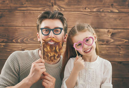 Grappig familie! Vader en zijn kind dochter meisje met een papieren accessoires. Beauty grappig meisje houden papieren bril op stok. Mooie jonge man met papier baard en een bril op stok. Stockfoto - 57628955