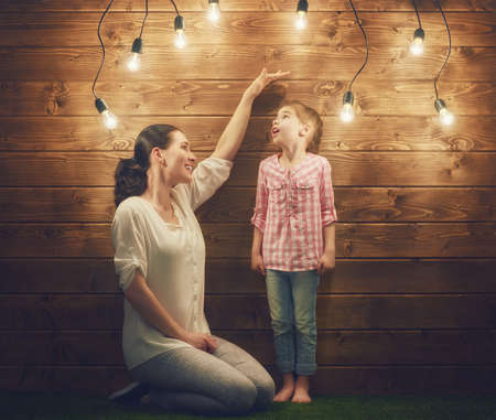 tall: Mother measures the growth of her child daughter at a wooden wall. Stock Photo