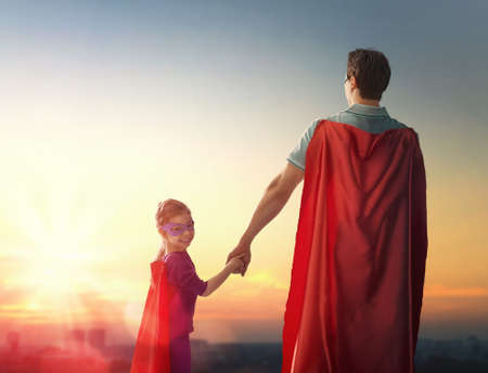 Amante de la familia feliz. Padre y su hija niña niño que juega al aire libre. Papá y su muchacha del niño en el vestuario de un super héroe. Concepto del día de padre. Foto de archivo - 57629148