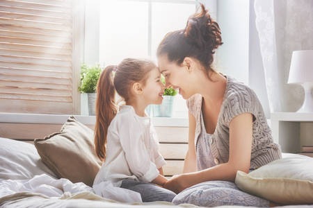 Happy loving family. Mother and her daughter child girl playing in bed.
