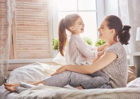 幸せな愛情のある家族。母とベッドで遊んで彼女の娘子女の子。 写真素材