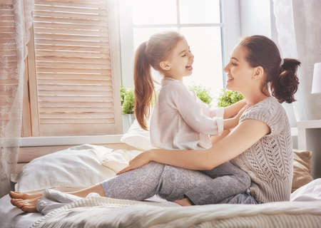 Happy loving family. Mother and her daughter child girl playing in bed. 版權商用圖片 - 57630424