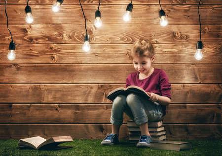 lamp light: Cute little child girl reading a book.