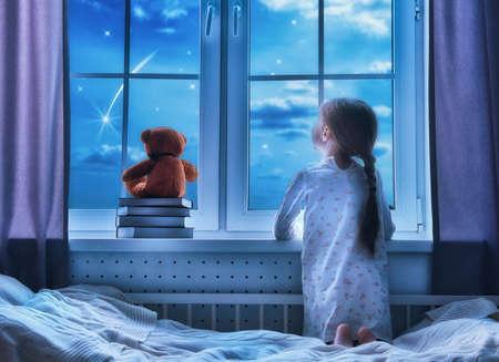Niña de niño lindo sentado en la ventana y mirando a las estrellas. Chica haciendo un deseo al ver una estrella fugaz en la noche antes de acostarse. Foto de archivo - 57630616