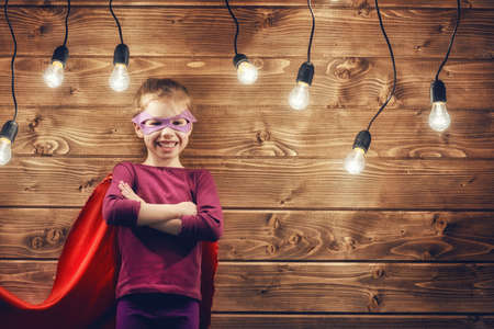 power concept: Little child girl plays superhero. Child on the background of wooden wall. Girl power concept. Stock Photo