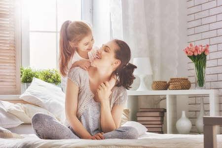 família amorosa feliz. Matriz e sua menina jogo da criança filha e abraços. Imagens