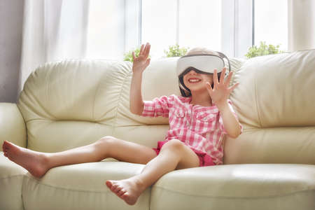reality: Cute little child girl playing game in virtual reality glasses. Stock Photo