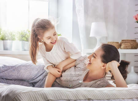 fond of children: Happy loving family. Mother and her daughter child girl playing in bed.