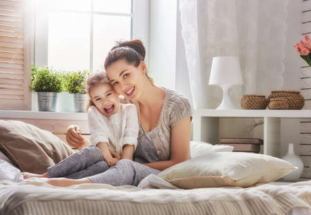 a young family: Happy loving family. Mother and her daughter child girl playing and hugging.