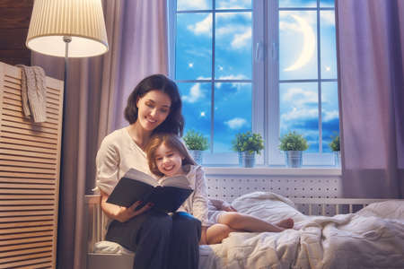 Family reading bedtime. Pretty young mother reading a book to her daughter. Stok Fotoğraf