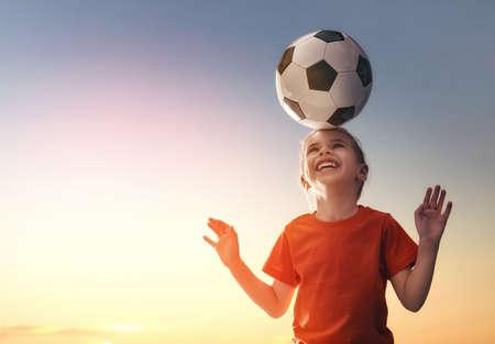 campeonato de futbol: Niño lindo sueños de convertirse en un jugador de fútbol. La muchacha juega al fútbol. Foto de archivo