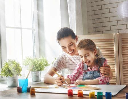 Famille heureuse. Mère et fille ensemble peindre. Femme adulte aide l'enfant fille. Banque d'images - 57836168