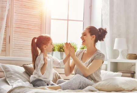 girl bedroom: Happy loving family. Mother and her daughter child girl playing together.