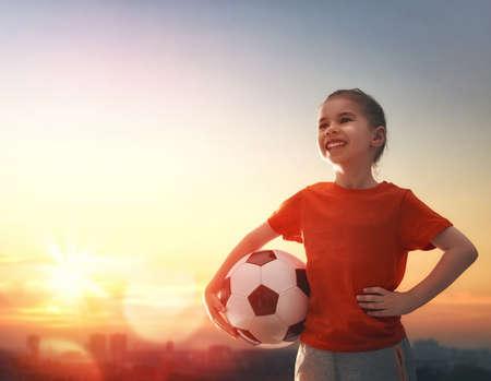 Leuk weinig kind droomt ervan om een ??voetballer. Het meisje speelt voetbal. Stockfoto - 57836175
