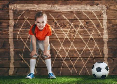 ballon foot: Jolie petite rêve de devenir un joueur de football de l'enfant. Fille joue au football. Banque d'images