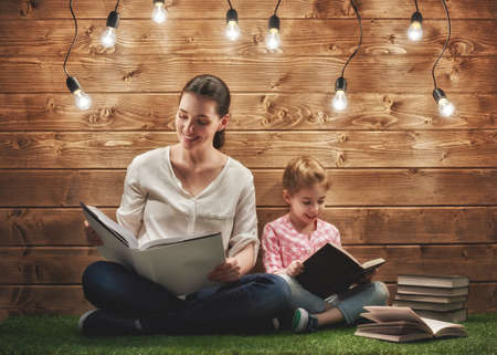 lady with the lamp: Happy loving family! Pretty young mother reading a book to her daughter Stock Photo