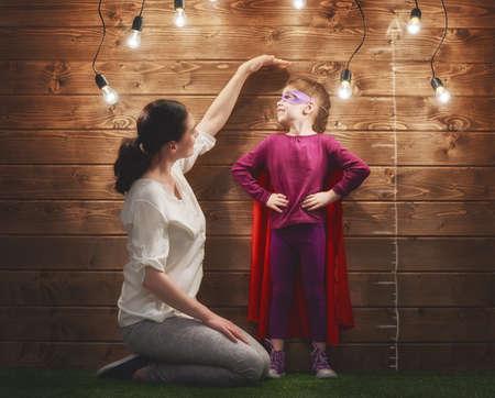 Moeder meet de groei van haar kind dochter op een houten muur. Stockfoto - 58370817